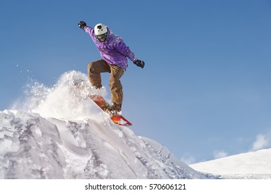 Stylish snowboarder with helmet and mask jumps from high snow slope