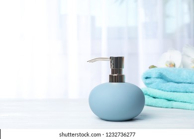 Stylish soap dispenser with flowers and towels on table. Space for text