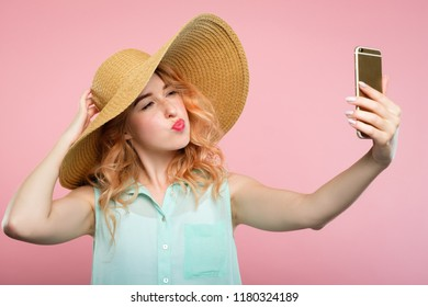 stylish social network influencer taking a selfie on mobile phone. fashion blogger posting a review on a summer fashion trends. young pretty girl in a big sunhat on pink background.