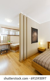 Stylish spacious bedroom with wooden floor and queen size bed. Behind the wall small modern bathroom