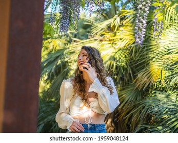A stylish Spanish girl is laughing while talking on the phone and posing in the natural background