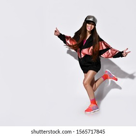 Stylish sporty brunette in a cap and a long bomber jacket, sneakers and long socks is jumping dancing is having fun on a light wall with a shadow, modern sports fashion