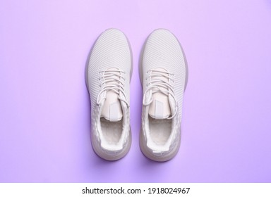 Stylish sporty sneakers on light violet background, top view