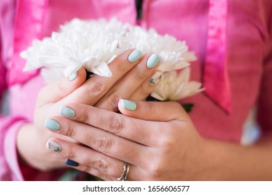 Stylish spring manicure in light tones. modern design of nails. Girl with beautiful nails holds white chrysanthemums