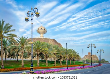 Stylish Streetlights, palm trees and roadside flower beds with the frankincense burner monument in the background.