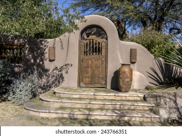 Stylish stucco rustic wood door archway entrance with steps to luxury home