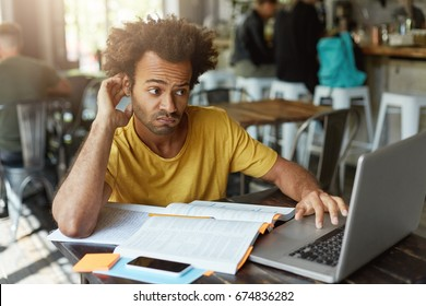 Stylish student with African hairstyle wearing casual clothes having doubtful look while looking at laptop computer not understanding new material trying to find good explanation in internet