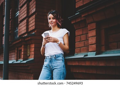 Stylish student in casual outfit checking email on modern telephone standing outdoors near university.Attractive young woman making payment online on smartphone device while looking straight