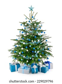 Stylish studio shot of a beautiful lush Christmas tree decorated in blue and silver, with matching gift boxes arranged in front of it, isolated on pure white background