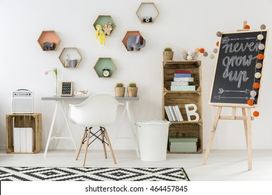 Stylish study space in a white room. By the wall shelf made of wooden boxes and blackboard with sign