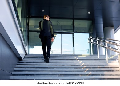 Stylish successful businessman goes up the stairs of the office building.