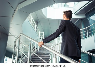 Stylish successful businessman goes up the stairs of the office building