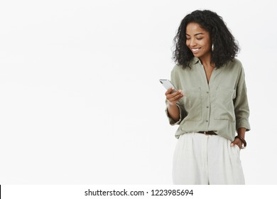 Stylish and successful dark-skinned female african entrepreneur checking mail box on way to office holding hand in pocket standing casually over gray wall holding smartphone smiling at gadget screen