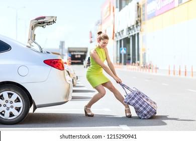 Stylish successful woman houls heavy big bag to car trunk in summer day.