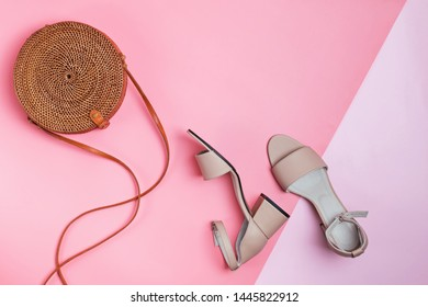 Stylish summer accessories isolated on pink background. Beige sandals and straw bag, stylish feminine outfit