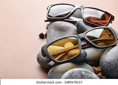 Stylish sunglasses and pebbles on color background