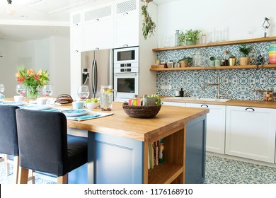 Stylish and sunny kitchen interior with accessories, wooden table and plants. Design space.