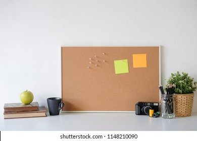 Stylish table Board and post it, book, pencil, camera  and coffee mug on table with wall.