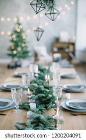 Stylish table setting for christmas family dinner with christmas tree on the background.