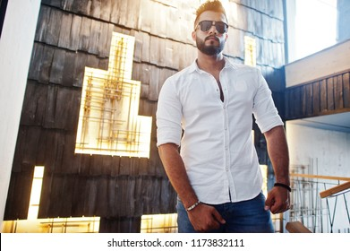 Stylish tall arabian man model in white shirt, jeans and sunglasses posed against light wall indoor. Beard attractive arab guy.