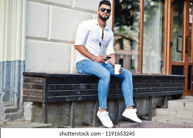 Stylish tall arabian man model in white shirt, jeans and sunglasses posed at street of city and hold mobile phone at hand. Beard arab guy with cup of coffee sitting and having rest.