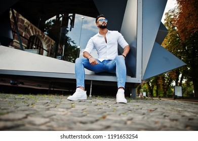 Stylish tall arabian man model in white shirt, jeans and sunglasses sitting at street of city. Beard attractive arab guy.