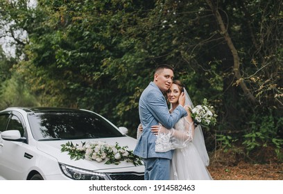A stylish, tall groom in a blue striped suit hugs a cute curly-haired bride in a white lace dress, standing on an asphalt road against the backdrop of a chic, expensive, decorated car.