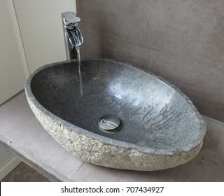 stylish tap and stone sink or trough with water flowing