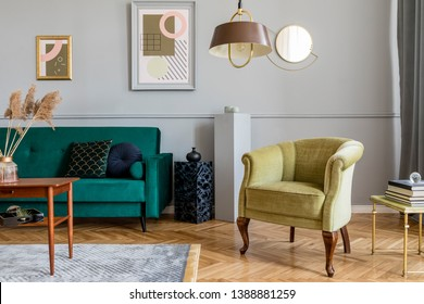 Stylish and tasty living room of apartment interior with elegant green velvet armchair and sofa, brwon table, design lamp and chic accessories. Abstract paintings on the gray wall. Luxury home decor.