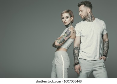 stylish tattooed couple in sportswear posing together, isolated on grey