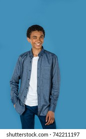 stylish teen boy isolated on blue looking at camera