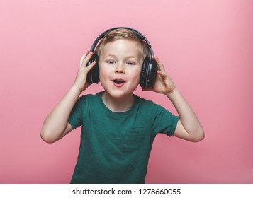 Stylish teen boy listening music in headphones and singing against pink background. School child listening loud music in wireless earphones and dancing