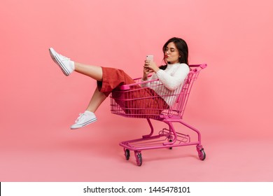 Stylish teen girl in culottes and white sweater sits in supermarket trolley. Model in glasses sends kiss and makes selfie on pink