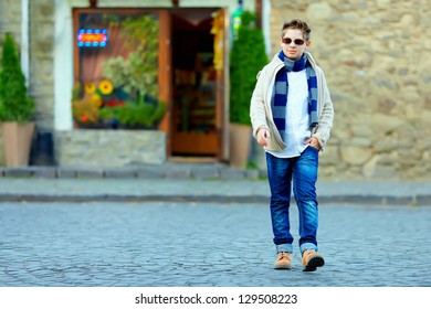 stylish teenage boy crossing the street of old town