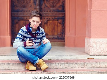 stylish teenage boy listens to the music on smart phone