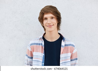 Stylish teenage boy with trendy hairstyle having dark eyes, pure skin and dimples on cheeks wearing shirt standing against white concrete wall looking directly into camera. Youth and fashion concept