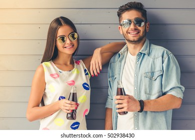 Stylish teenage couple in sun glasses holding bottle of soda water, looking at camera and smiling, on gray background
