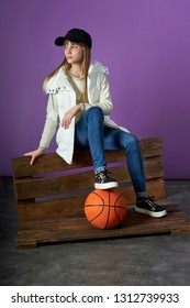 stylish teenager with a basketball ball. Young girl posing in the studio, purple background. Casual clothes for city, sports, cap, waistcoat, jeans, sneakers.