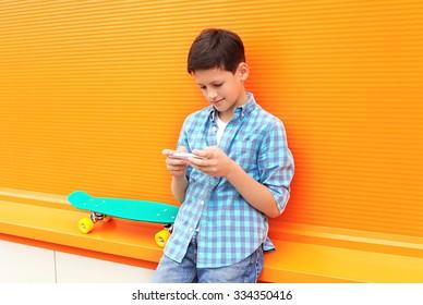 Stylish teenager boy with skateboard using phone in city over orange background