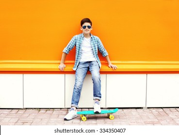 Stylish teenager boy wearing a checkered shirt, sunglasses on skateboard in city over orange background