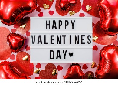 Stylish text frame lightbox with the inscription happy Valentine's day. Pink, red and beige hearts all around. Foil balloons top view of Valentine's Day. Copyspace. - Shutterstock ID 1887956914