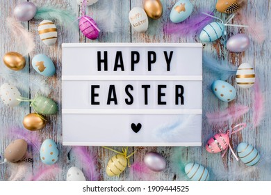Stylish text frame of the lightbox with the inscription happy easter. Pink, blue, white, gold, and yellow eggs are everywhere. Colorful Easter eggs top view. Copyspace. - Shutterstock ID 1909444525