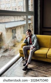 stylish thoughtful man sitting on yellow sofa and looking at window