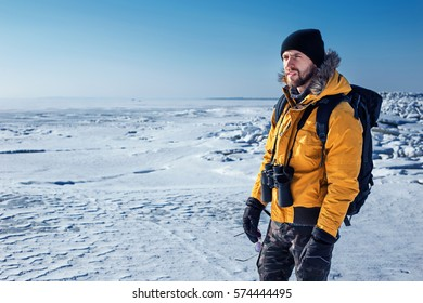 Stylish Traveler Man with backpack mountaineering.  He enjoys the view of winter nature. Travel Lifestyle concept. Winter expedition vacations outdoor