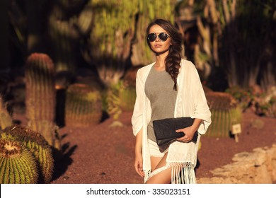 Stylish trendy beautiful girl with long braid posing in t-shirt and shorts with handbag against cactuses. Outdoor summer portrait