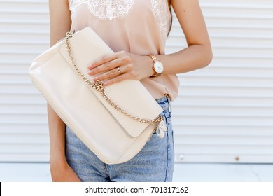 Stylish trendy casual woman's outfit. Woman in beige cami silk top, blue denim jeans, clutch bag, gold watch, rings posing against white street wall. Street fashion. Details of everyday look.