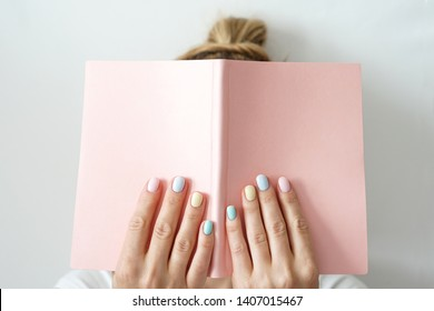 Stylish trendy color female manicure . Woman's hands keep pink note pad