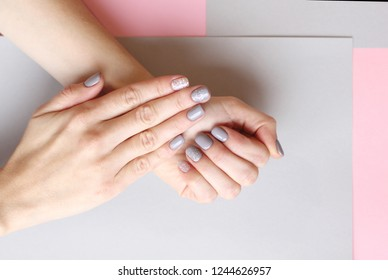 Stylish trendy female grey manicure. Beautiful young woman's hands on pink and grey pastel background . Minimalist manicure trend. Copy space. Top view, flat lay.