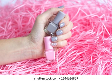 Stylish trendy female grey manicure. Beautiful young woman's hands on pink pastel background with nail polishes. Minimalist manicure trend. Top view, flat lay.