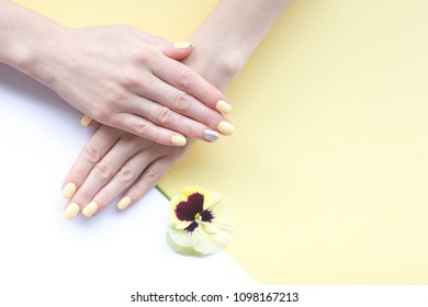 Stylish trendy female manicure. Beautiful young woman's hands on yellow and white background.